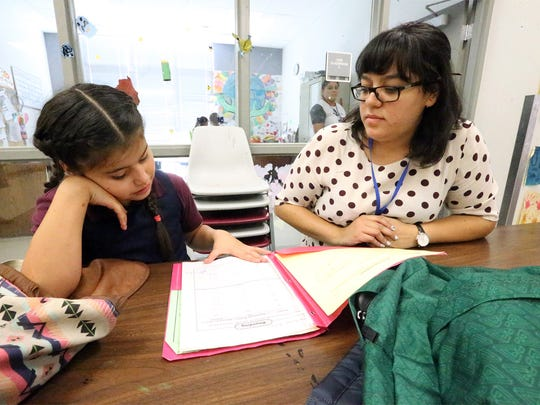Evelyn Palacios, a third grade student at Zavala School gets homework help from Anahi Gomez during the after school program at Project Vida.