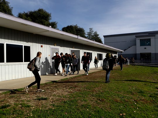 Shasta High School students make their way across campus Monday in front of some of the portable classrooms at the school. A recently passed bond measure would allow the school to replace portable buildings with permanent ones.