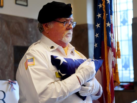 Vietnam Veterans Post 995 Honor Guard member, Ronnie Butler holds the American Flag in his arms after performing the Thirteen Folds of the Flag during the Vietnam Veterans Day event, Thursday, March 29.