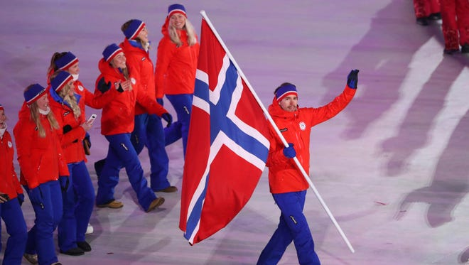Emil Hegle Svendsen of Norway arrives with the flag during the parade of athletes in the opening ceremony.