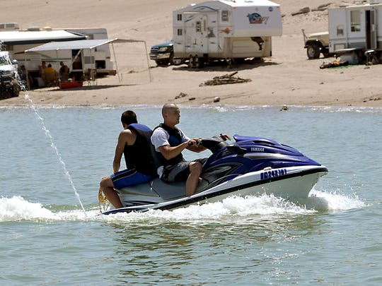 Cody Romero of Los Lunas, N.M., maneuvers a personal watercraft along the shores of Elephant Butte Lake with Mark Montoya of Albuquerque. If you go boating, wear a life jacket. Most boating fatalities occur from drowning.