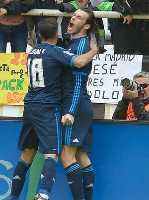 Bale, right, celebrates with teammate Lucas Vazquez after scoring madrid's third goal.