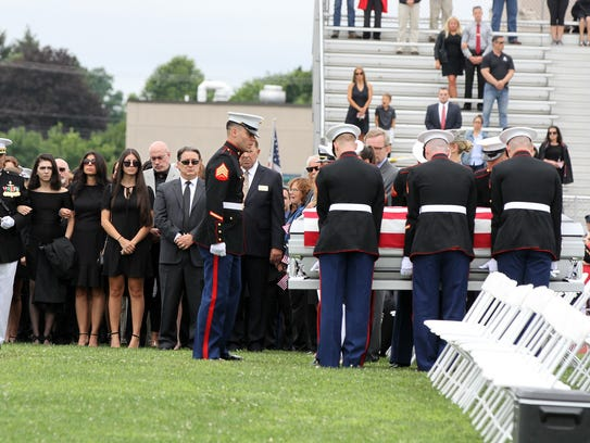 Family members mourn as the casket is carried onto