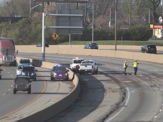 Workers clean the northbound lanes of Interstate 75