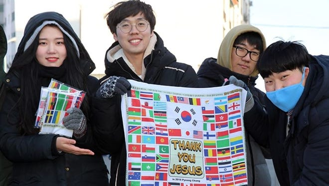 College students, volunteering with the United Christian Churches of Korea, display the bandanas they are giving away outside the Olympic Park in Gangneung on Feb. 10.