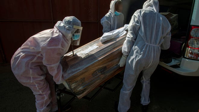 Funeral home workers in protective suits carry the coffin of a woman who died from COVID-19 into a hearse in Katlehong, near Johannesburg, South Africa. The worldwide death toll from the coronavirus eclipsed 1 million on Tuesday, nine months into a crisis that has devastated the global economy, tested world leaders' resolve, pitted science against politics and forced multitudes to change the way they live, learn and work.