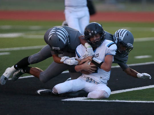 TLCA Eagle Kaiden Kirkland is tackled in the end zone by two Grape Creek Eagles during the first quarter of Friday night's game in Grape Creek Sept. 15, 2017.