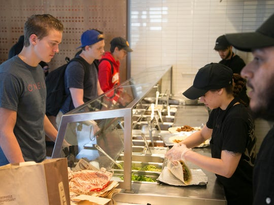 Marc Rigau, 17, orders a chicken burrito at a Chipotle