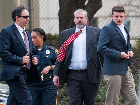 A.C. Smith, right, arrives for a hearing at the county