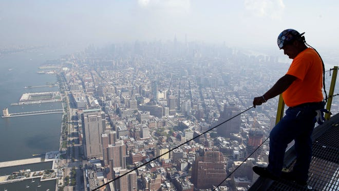 FILE - In this Aug. 26, 2014 file photo, a construction worker takes in the view from the communication rings on top of One World Trade Center in New York. The Commerce Department issues its third and final estimate of how fast the U.S. economy grew in the July-September quarter on Tuesday, Dec. 23, 2014. (AP Photo/Seth Wenig, File)