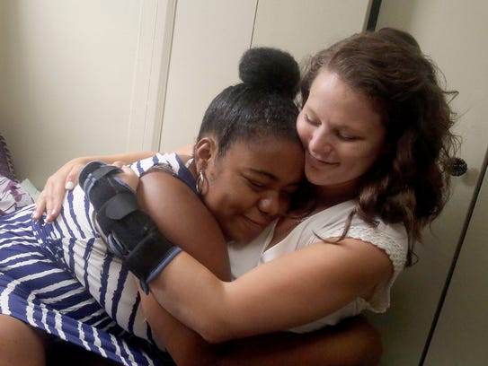 Shauntia Akins, 22, lett, hugs Fiona Wilkes, manager