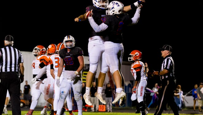Campbell County's John Porter (11) and Drew Jordan (2) celebrate after a touchdown during a game between Campbell County and Powell at Campbell County High School in Jacksboro, Tennessee on Friday, September 29, 2017.