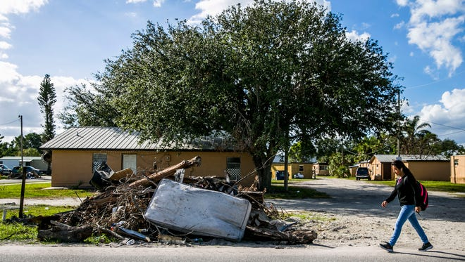 A pile of debris sits beside a road in Immokalee on Wednesday, Dec. 6, 2017. It has been three months since Hurricane Irma hit Southwest Florida, and communities, including Immokalee, are still picking up the pieces.