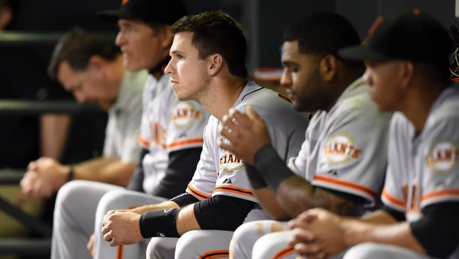 San Francisco Giants catcher Buster Posey (28) and teammates watch from the dugout in the ninth inning against the Colorado Rockies at Coors Field. The Rockies won 2-1.
