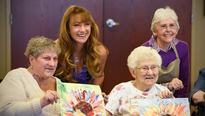 Jane Seymour poses for a photograph with seniors following an art class at St. Benedict's Senior Community Friday, May 5, in St. Cloud.