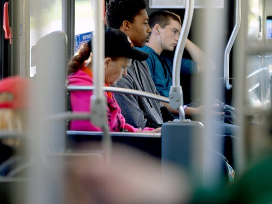 Riders pass the time on a CATA bus Tuesday, Sept. 27, 2016, while riding the No. 1 route which goes from downtown Lansing to the Meridian Mall.