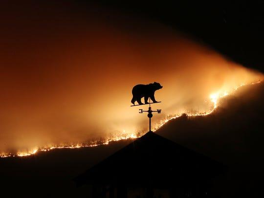 A weathervane sits on top of a barn over a wildfire near Dillard, Ga., Monday, Nov. 21, 2016. (Curtis Compton /Atlanta Journal-Constitution via AP)