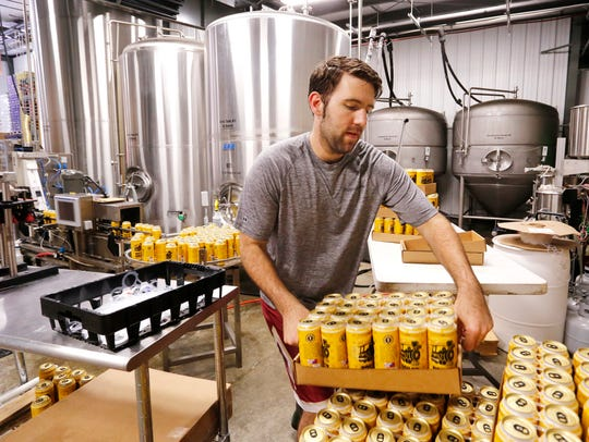 David Thieme stacks cases of Boiler Gold American Ale