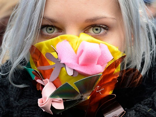 A climate activists with a colorful mask attends the