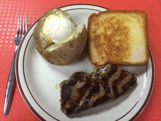 The Tuesday special: Ribeye steak with baked potato and grilled Texas toast. It also includes a salad