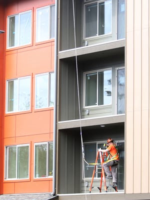 A construction worker climbs a ladder while working on one of the balconies of the Arendal on Viking apartment complex in Poulsbo on Friday.