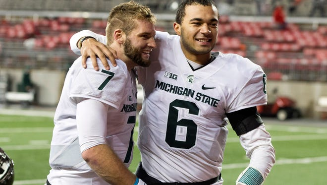 Michigan State quarterbacks Tyler O'Connor (7) and Damion Terry (6) celebrate after defeating Ohio State on Nov. 21 at Ohio Stadium. With starter Connor Cook out injured, the Spartans' two backups help to engineer a 17-14 upset that propelled MSU to a Big Ten championship and the College Football Playoff.
