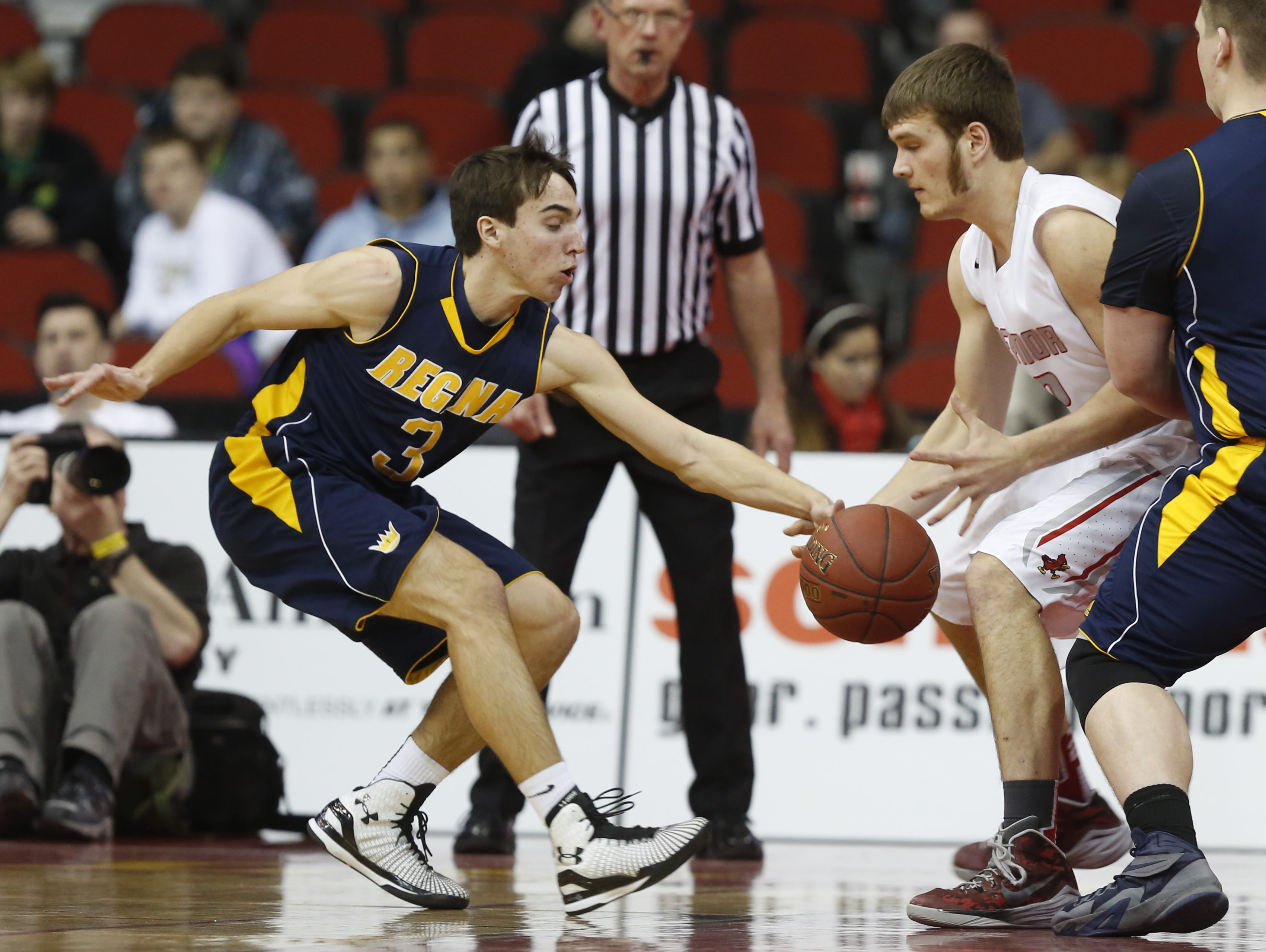 Regina's Nathan Stenger swipes the ball away from Treynor's Jacob Flathers Friday, March 13, 2015, at 2A Boys State Basketball Tournament championship game at Wells Fargo Arena in Des Moines.