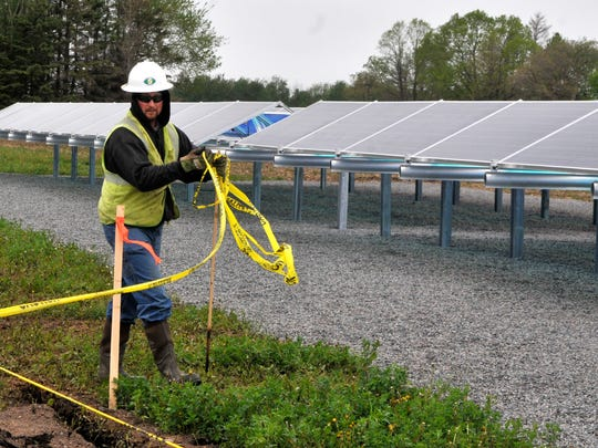 Mike Siemers removes the plastic tape surrounding the new array of solar panels at Stearns Electric Association's St. Joseph facility. Workers dug a 445-foot trench May 18 that would connect the array.