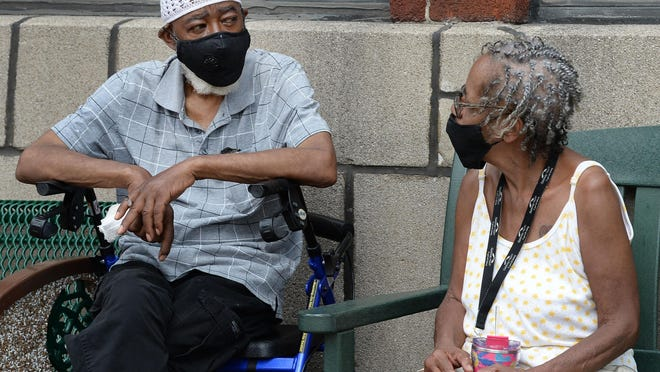 "Robert Chandler, 70, and his wife Sadie Chandler, 69, residents of the Richford Arms apartments in Erie, sit outside Wednesday. One-third of Erie County COVID-19 cases are African-Americans. ""I am susceptible to the virus because of pre-existing conditions,"" said Robert Chandler. ""I'm very concerned. I don't see a lot of people wearing masks."""