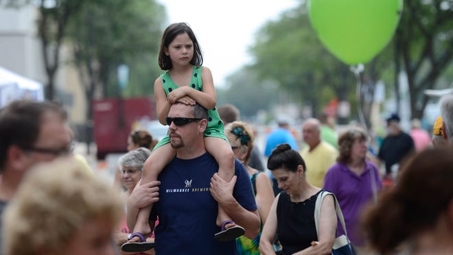 Tom Sieber walks through the Artstreet event Saturday with his five-year-old daughter Jillian on his shoulders.