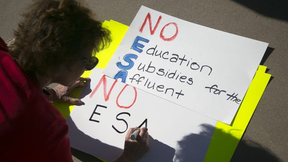 Sandy Kravetz, of Scottsdale, writes out a sign, while