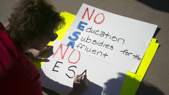 Sandy Kravetz, of Scottsdale, writes out a sign, while protesting with several dozen other people rallying against an expanded school voucher program, as Arizona lawmakers prepare to advance legislation that would expand the state's school voucher program, at the Arizona State Capitol in Phoenix on Thursday, April 6, 2017.