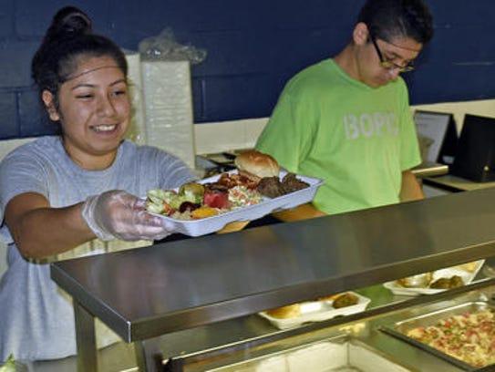 Andrea Lira and Carlos Jimenez serve healthy meals