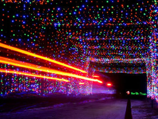 A car passes through a tunnel of Christmas lights at