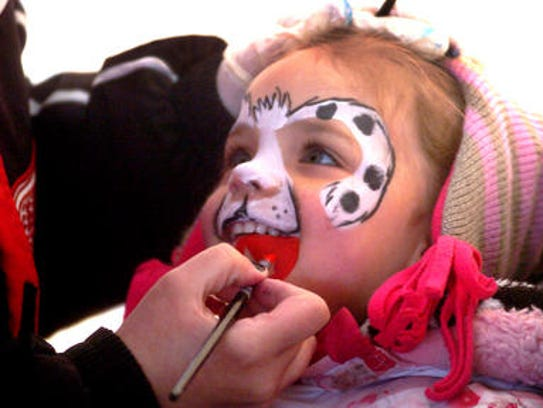 Molly Benson gets her face painted at the Huron Valley egg hunt in this 2015 photo.