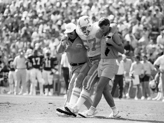 Tennessee offensive tackle Daryle Smith (57) gets helped off the field by a couple of Vols trainers after suffering an injury against Auburn on Sept. 27, 1986.