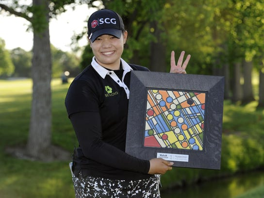 Ariya Jutanugarn stands with the LPGA Volvik Championship