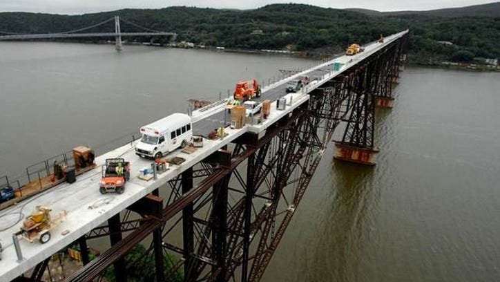 Below, The railroad bridge's platform is covered with cement pads, which weigh approximately 30,000 pounds each. The Mid-Hudson Bridge is pictured in the background.