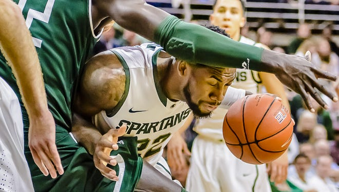 Branden Dawson (right) of MSU fouls Olalekan Ajayi of Eastern Michigan as Dawson drives the lane to the basket during their game Wednesday December 17, 2014 in East Lansing.