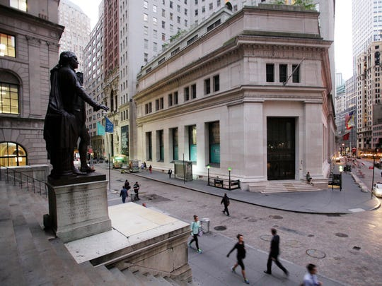 In this Oct. 8, 2014, photo, people walk to work on Wall Street beneath a statue of George Washington, in New York. Stocks moved higher in early trading Wednesday, July 27, 2016, led by gains in technology stocks after Apple soared on a strong earnings report. Investors are looking ahead to a decision on interest rates from the Federal Reserve, which wraps up a two-day policy meeting later in the day.