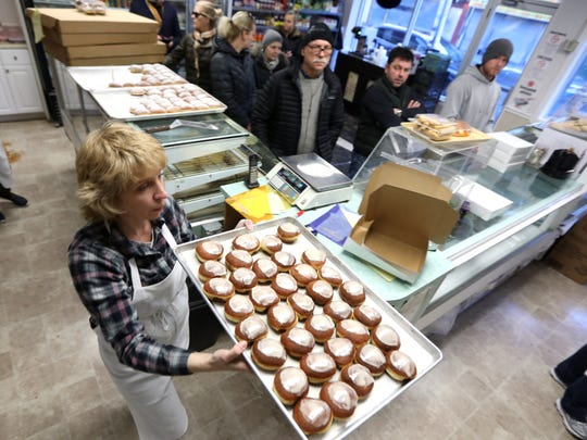 Natalie Mazur brings out a fresh batch of paczkis while customers wait patiently.