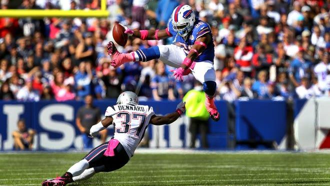 Bills running back Boobie Dixon leaps over Patriots defender Alfonzo Dennard (37) for extra yards. The Bills fell to the Patriots 37-22.