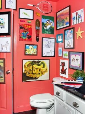 A boys bathroom designed by Brian Patrick Flynn features framed children's art on the walls, perfect for displaying all the newest kids artwork coming in.
