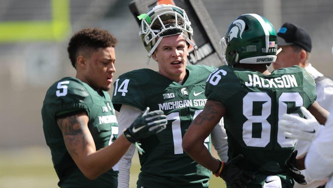 Michigan State quarterback Brian Lewerke, center, talks with receivers Hunter Rison, left, and Trishton Jackson on the sideline during the spring game at Spartan Stadium on April 1, 2017.