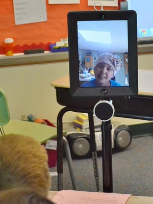 Elysia Mirales talks with a classmate at Oconto Elementary School through a telepresence device, which allows her to attend her classes from home while she battles cancer.
