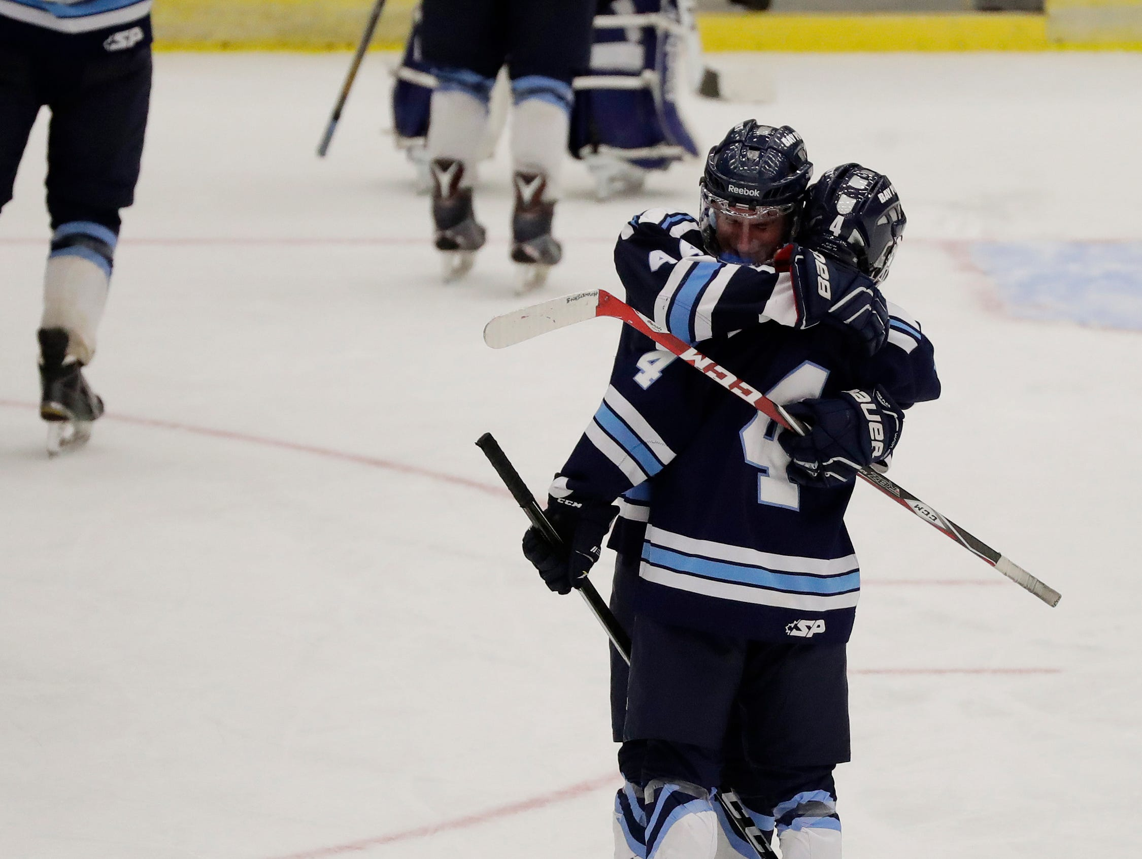 Bay Port forward Mike Messerschmidt (4) hugs teammate Max Moore (44) after a quarterfinal match against Sun Prairie at the WIAA state hockey tournament at the Alliant Energy Center on Thursday. The Pirates lost 3-2 in their first state appearance.