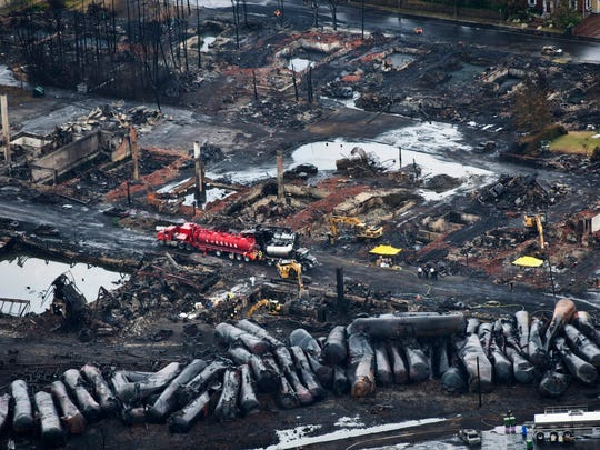 Workers comb through debris on July 9, 2013, after a train derailed, causing explosions of railway cars carrying crude oil, in Lac-Megantic, Quebec. A government watchdog says federal regulators are failing to refer serious safety violations involving freight rail shipments of crude oil for criminal prosecution.