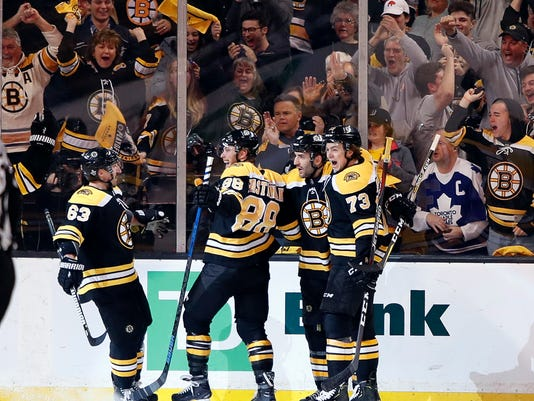 Boston Bruins' Brad Marchand, David Pastrnak, Patrice Bergeron and Charlie McAvoy, from left, celebrate after Pastrnak scored against the Toronto Maple Leafs during the first period of Game 2 of an NHL hockey first-round playoff series in Boston Saturday, April 14, 2018. (AP Photo/Winslow Townson)