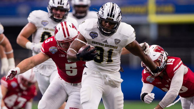 Western Michigan Broncos running back Jarvion Franklin (31) tries to elude Wisconsin Badgers linebacker Garret Dooley (5) and safety Leo Musso (19) during the second half at AT&T Stadium. The Badgers won 24-16.