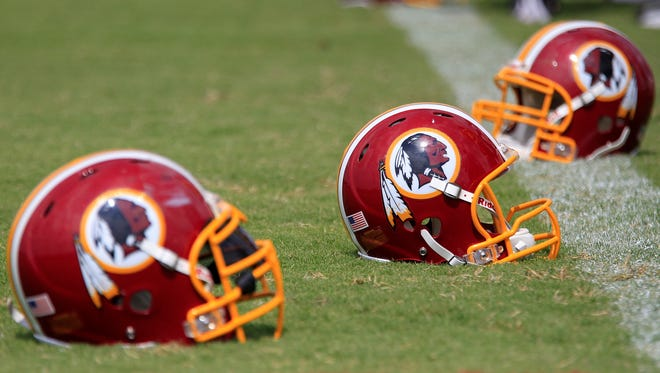 Washington Redskins players' helmets rest on the field during 2013 NFL training camp at the Bon Secours Washington Redskins Training Center.